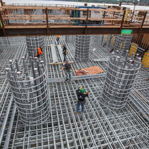 Ironworkers arrange layer upon layer of steel reinforcements in the new bridge's foundations.